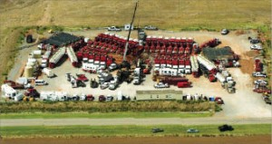A Weatherford well completion site in Canadian County, Okla., in the Woodford Shale is surrounded by close to 30 frac pumps, the number required to pump 100 bbl/min at over 10,000 psi surface treating pressure. The black water tanks (rear left) hold water that is being pulled out by the adjacent truck and transported to the frac pumps.