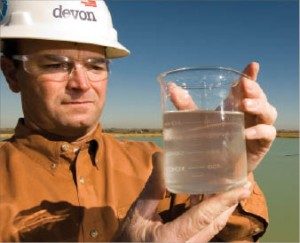 Jay Ewing, completion construction manager for Devon Energy, checks water that has been treated at one of Devon's recycling units in the Barnett Shale. Devon recovers about 85% of flowback used during the completion phase of the area's wells.