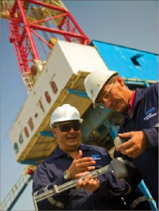Baker Hughes drilling fluid engineers in Kazakhstan use a mud balance to check the density of a drilling mud sample. The company says that its drilling and evaluation businesses were more stressed in '09 while its completions and production sector held up.