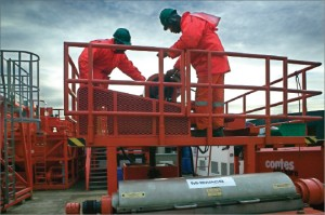 Two M-I SWACO drilling fluid specialists monitor the centrifuge system, part of the solids control systems used to keep the fluid clean.