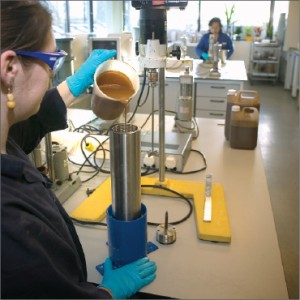 A lab technician pours drilling fluid into a pressure cell for proper stirring with the Heidolph stirrer prior to viscosity testing.