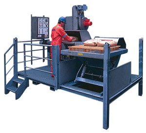Figure 4: A sack-handling unit elevates sacks to the most ergonomic height. The operator slides the sack onto the roller table and pushes it into the machine, which automatically starts and performs the slitting, emptying and feeding sequence, including packing the emptied sack into the waste bag. Courtesy of National Oilwell Varco