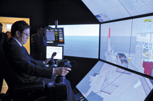 Daikichi Kukuta from Japan Radio Company attempts to safely land a container on a rig using the crane simulator at the MOSAIC II, where different simulators can be integrated with one another for a team-based training experience.