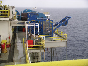 The umbilical winch, which extends over the side of the rig, raises and lowers the pumps to the seabed and serves as a conduit for power and communication.