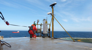 A Fugro service engineer installs a real-time helideck and environmental monitoring system to aid operational planning and safety.