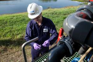 A Baker Hughes water treatment specialist captures a water sample from an H2prO treatment unit that converts produced water into a reusable resource for hydraulic fracturing. A typical hydraulic fracturing operation requires 2.5 million to 4 million gallons of water.