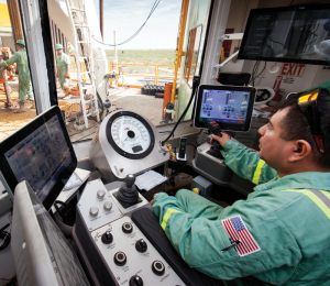 A driller controls the drilling process from his cabin on Precision Rig 575. Precision Drilling began its Target Zero program in 2000 to reinforce and improve policies and practices to meet the goal of zero injuries.