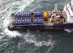 "A boat using ""slider tanks"" transports cuttings to shore for further treatment and disposal in the North Sea. The cuttings were blown from a rig without the use of a crane. A transfer line floats in the water."