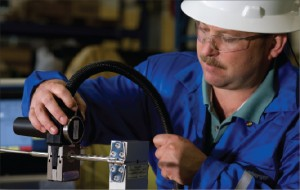 A Schlumberger operator splices an electric cable with the Intellitite connector. The nonwelded connector incorporates independent, redundant metal-to-metal seals and a cable-anchoring device to isolate the seal from any mechanical loading. During installation, seals are tested using a microleak detection system. Source: Schlumberger