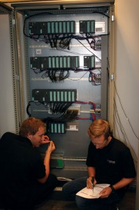 Technicians interface the HIL simulators to the control system replica PLC rack in the HIL testing lab. Setting up the HIL lab involves connecting a vessel's main control systems to a simulated rig that is an exact replica of the actual vessel, which establishes a virtual world for the control systems to interact. Source: Øyvind Smogeli