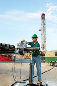 An NOV Tuboscope technician inspects drill pipe on a rig site; the service is typically performed after every other well.