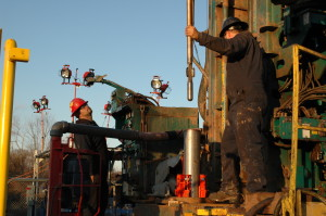 APS Technology crew members install an MWD string in a drill collar on a rig. The company's SureShot MWD system includes pressure-while-drilling, propagation resistivity and weight, torque and bending on bit sensor options.