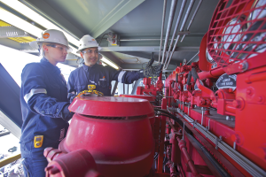 BHP operations engineers inspect equipment on a new H&P FlexRig 5 in the Eagle Ford. BHP is reducing its North American land operations next year from 40 rigs to 26, which is expected to help the company focus on safety and operational performance.