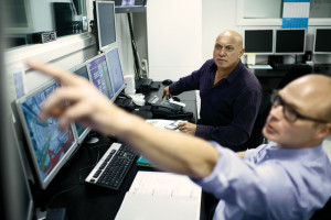 Maersk Training instructors Kim Noe (front) and Denis Edmonds (back) observe student behaviors and actions from the control room behind the drilling simulator during a technical exercise.