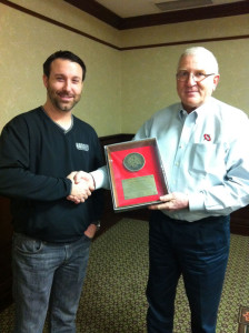 Joe Hurt presents a chairman's plaque to Hodges Trucking's Justin Hodges