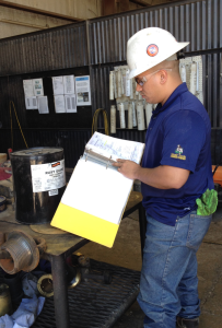 A worker reviews the safety data sheet for required PPE before putting a protective coating on thread connectors for drill pipe at the Quail Tools rental facility in Odessa, Texas. Quail Tools is a subsidiary of Parker Drilling.