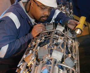 A worker inspects an Expro riser control module, which completes a full landing string assembly when integrated with an in-riser SSTA.