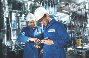 : DNV GL – Oil and Gas workers inspect testing devices at a sand test laboratory. The company's updated recommended practice provides a set of guidelines to manage sand through the life of a well and promotes making the best use of available technologies and methods.