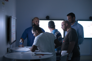 Robert Howell (back right), a technical instructor with Maersk Training, helps students from Rowan start a well control simulator exercise on 22 July in Houston. In the five-day course, students split their time between the classroom and the simulator, with human factors built directly into the technical training.